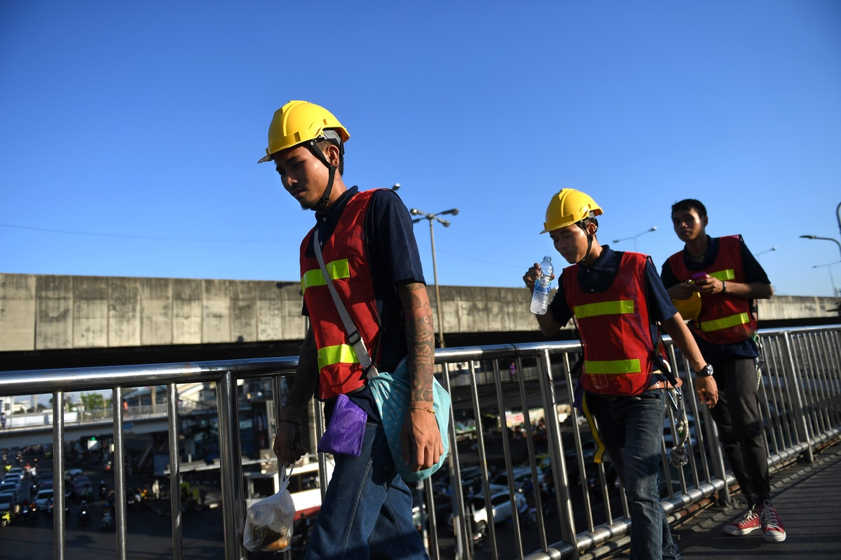Thai workers walking to a building construction site in Klong Toey district in Bangkok