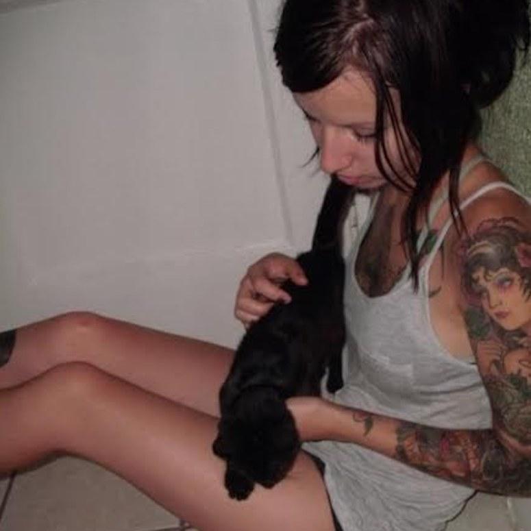 brunette girl with tattoos holding black kitten