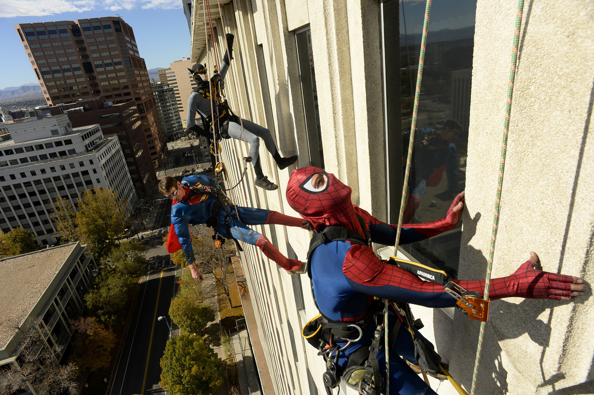 Halloween workers scale the side of the Capitol Center Trask Bradbury, dressed as Spiderman, Brent Seely dressed as Superman and Martin Barnett, dressed as Batman all from Gemini Rope Access Solutions