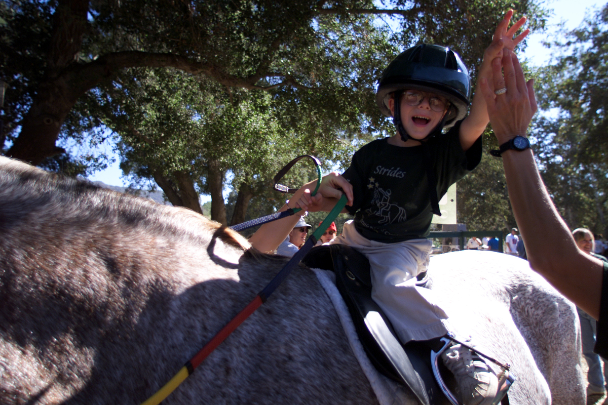 Young competitor Judd Tennant (cq), 5, who has cerebral palsey, gets a high five from his mom before