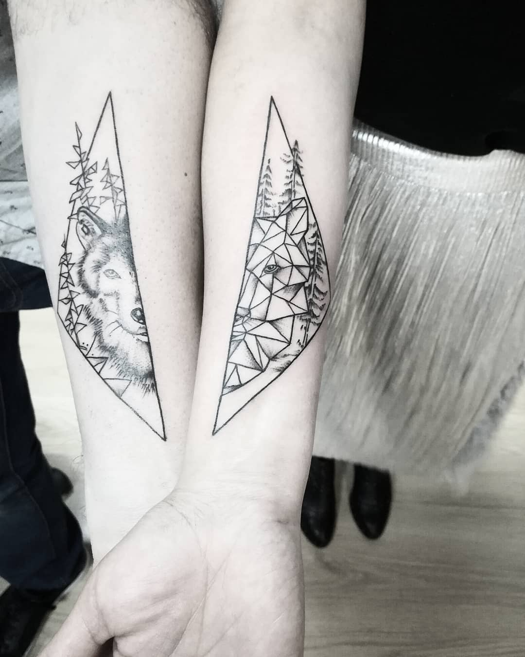 matching tattoos of geometric wolf and geometric background