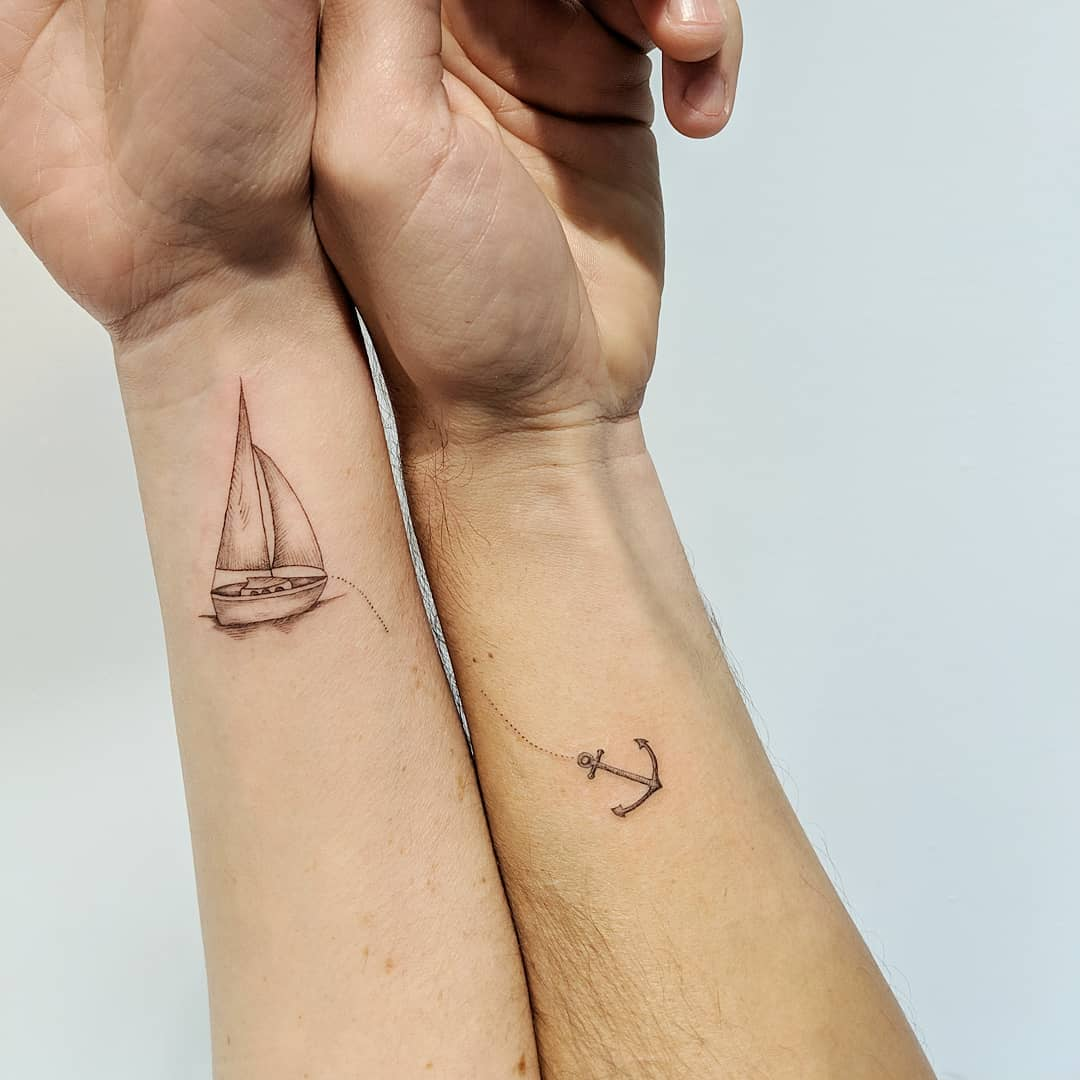 matching tattoo on wrists of a boat and attached anchor
