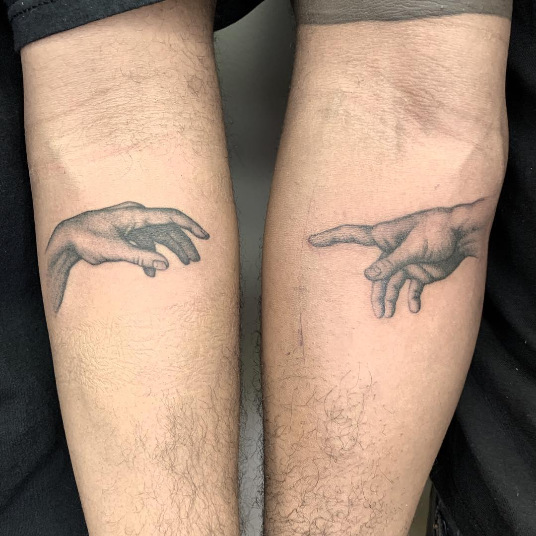 matching tattoo of two hands from divine creation