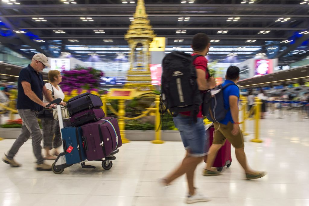Tourists walk while carrying their luggages at the departure area of Suvarnabhumi airport in Bangkok