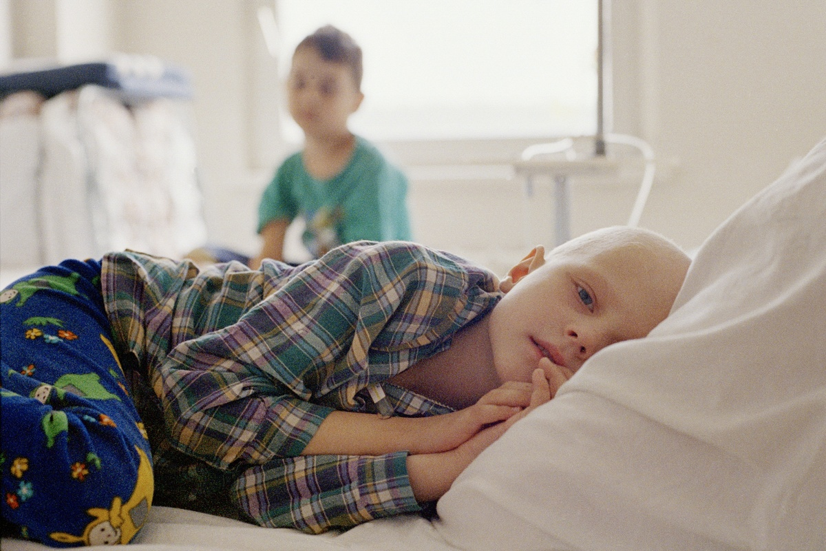 young cancer patient lies in a hospital bed