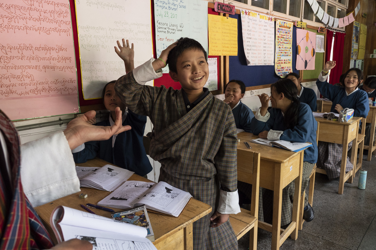 bhutan school kids hand raised smiling school classroom