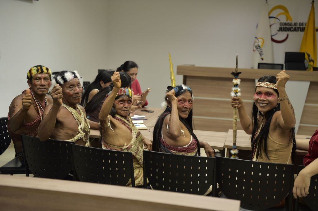 Waorani indigenous people sitting in courtroom raising fists