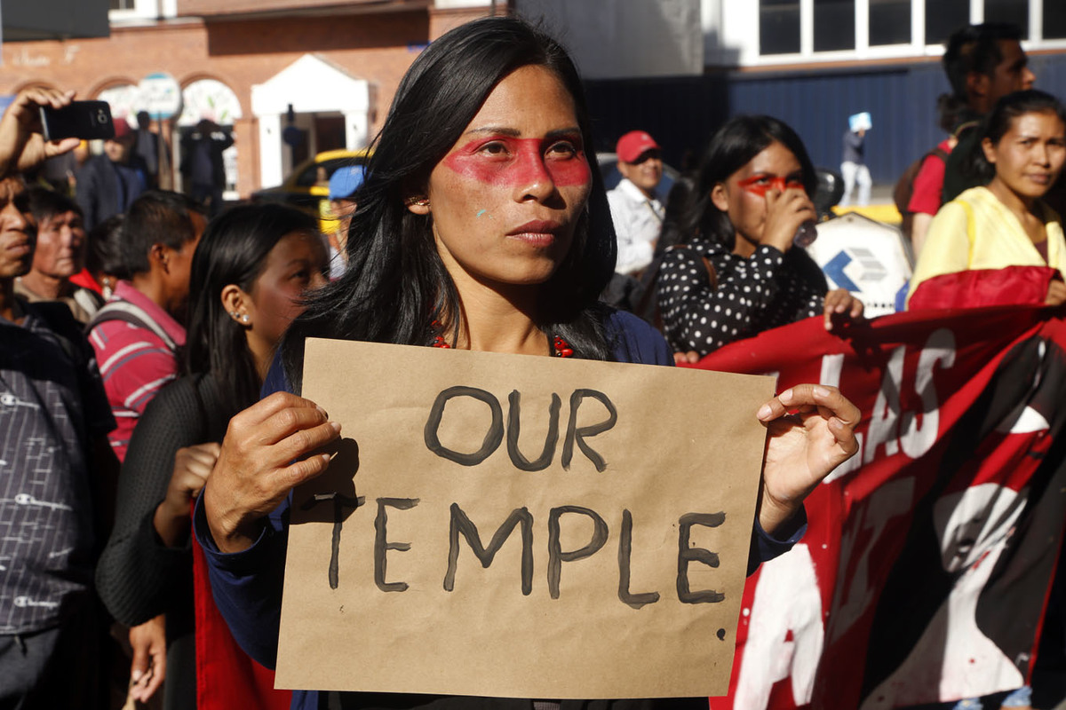 Waorani indigenous woman holding protest sign outside the ministry of natural resources