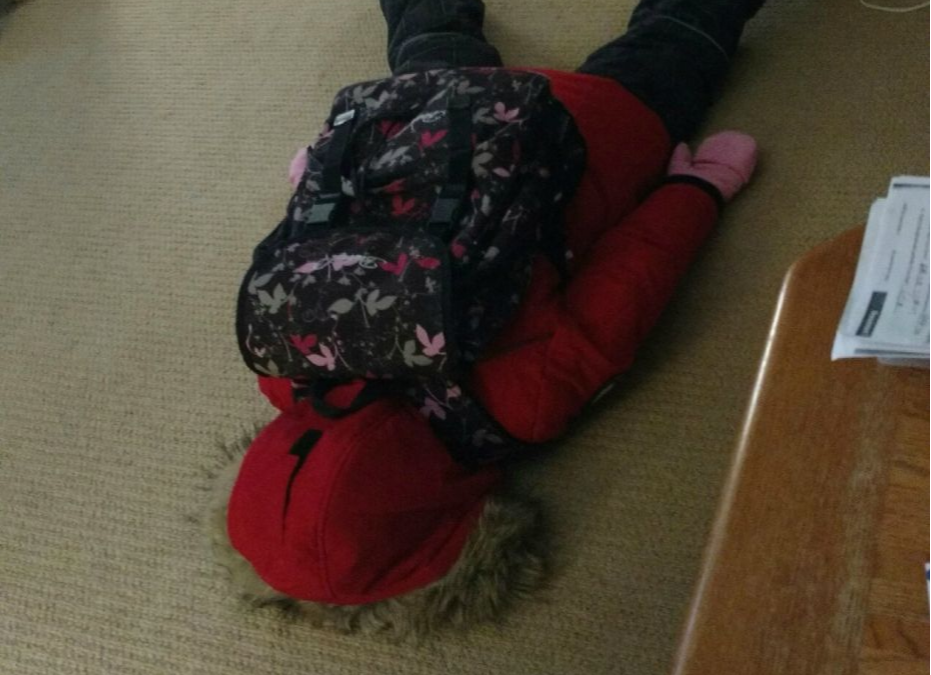 Girl in a red jacket lying on the floor refusing to go to school