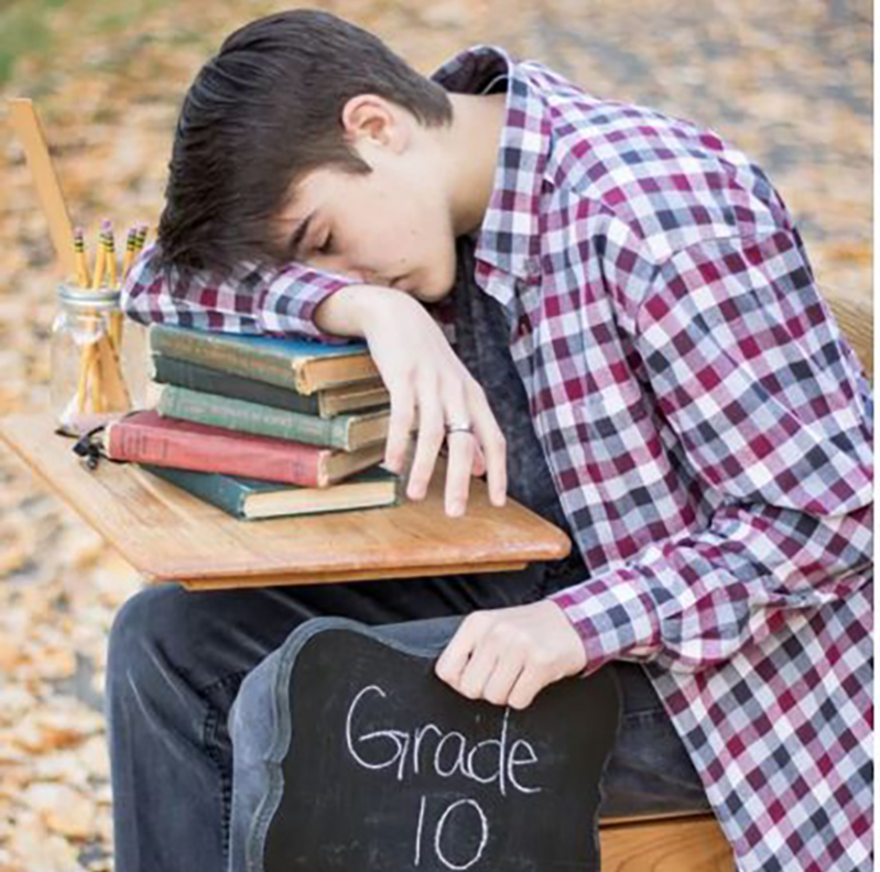 Boy asleep on his desk set during a photoshoot