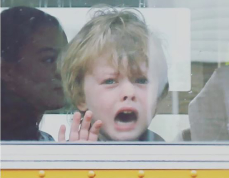 a young boy screams for his parents behind the bus window