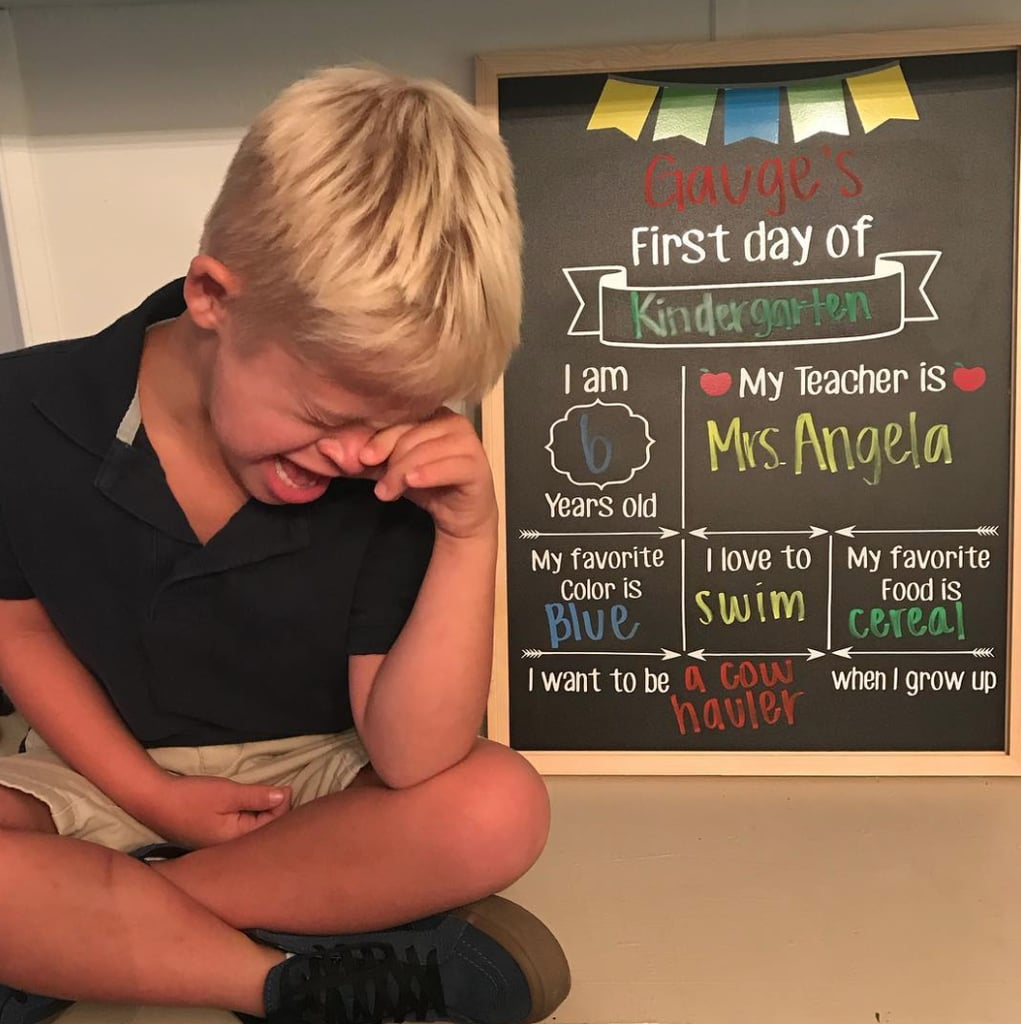 Kindergarten boy crying in front of a blackboard with facts about him