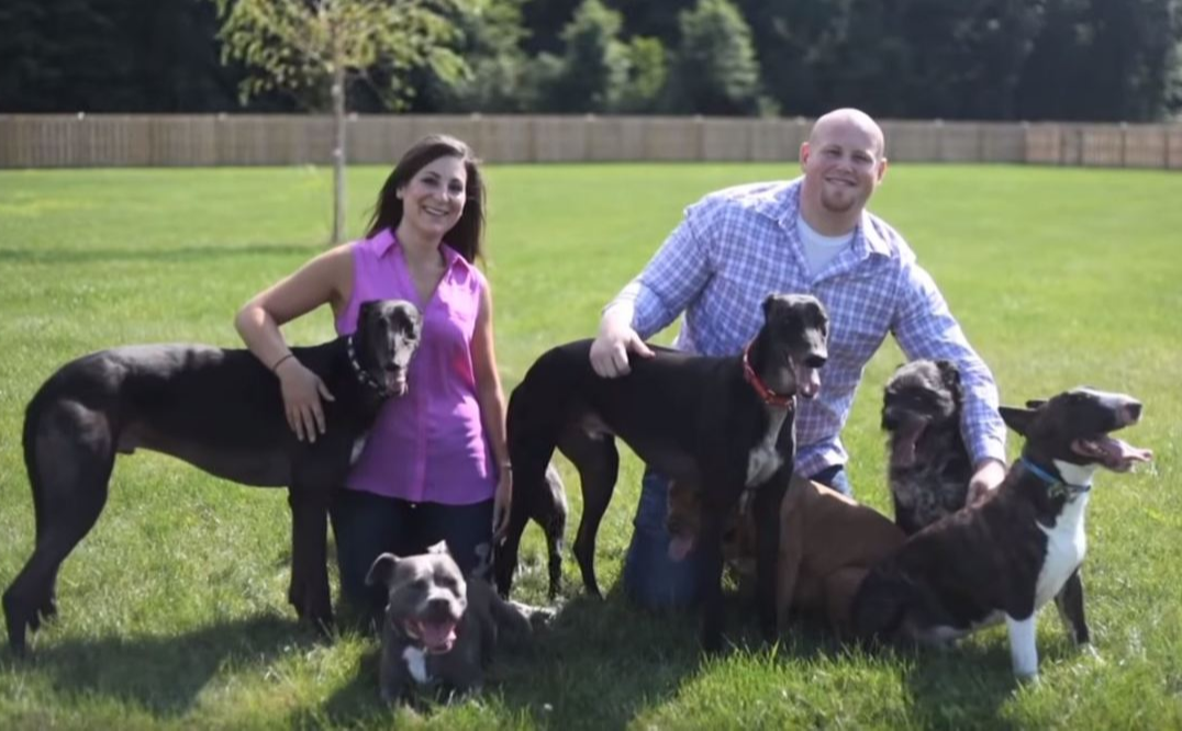 Chris and Mariesa with their eight dogs in their yard