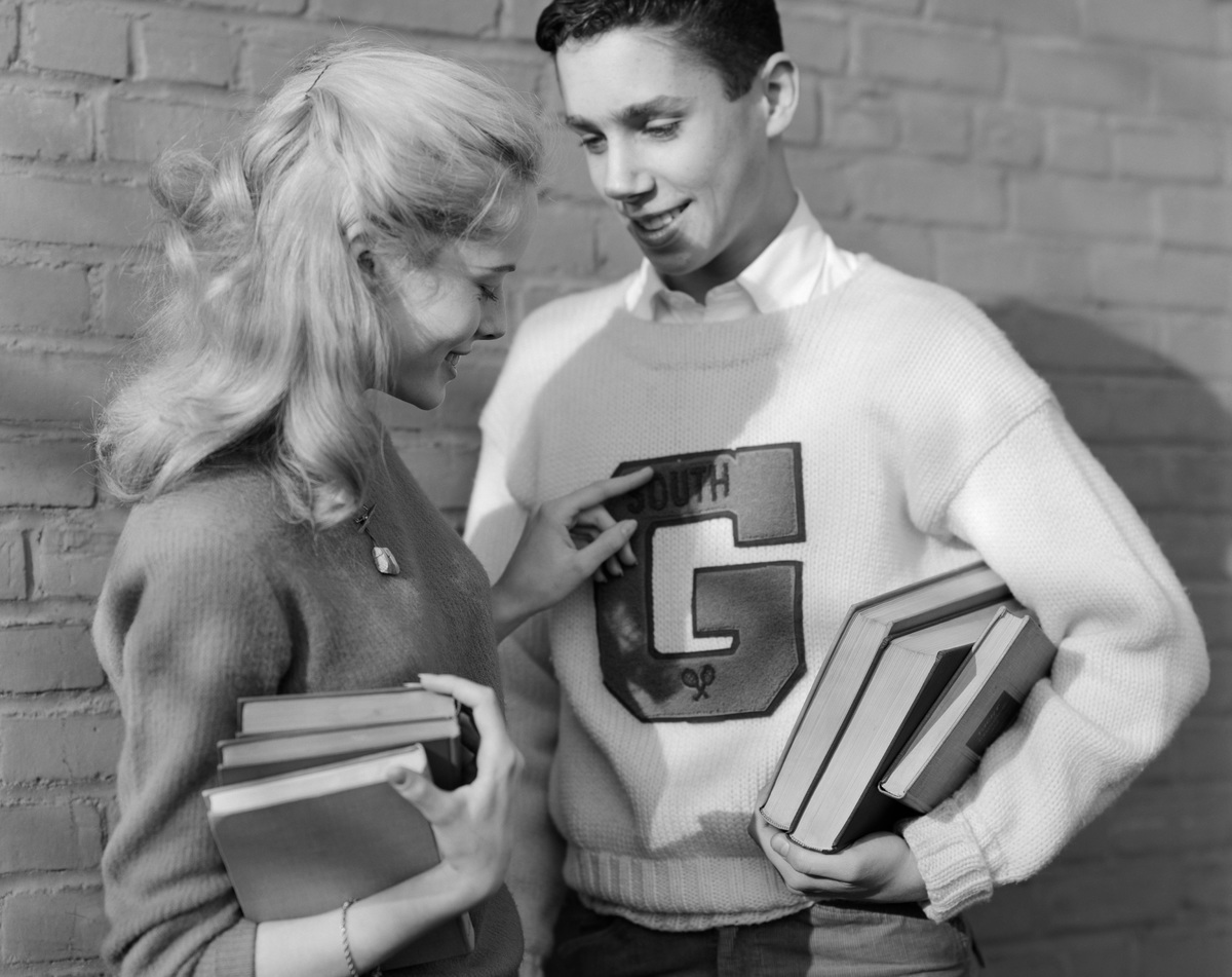 1950s TEENAGE COUPLE HOLDING BOOKS SMILING LEANING AGAINST WALL BOY WEARING VARSITY LETTER SWEATER