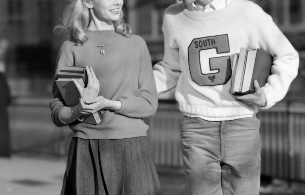 1950s TEENAGE BOY WEARING VARSITY LETTER SWEATER WALKING GIRL HOME AFTER SCHOOL