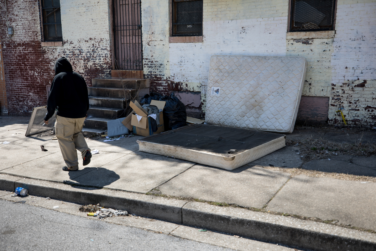 A resident walks past old mattresses on Argyle Avenue in the Upton neighborhood of Baltimore, Md.