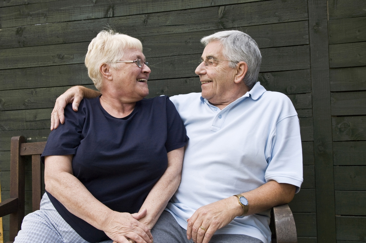 happy smiling senior couple sitting on bench