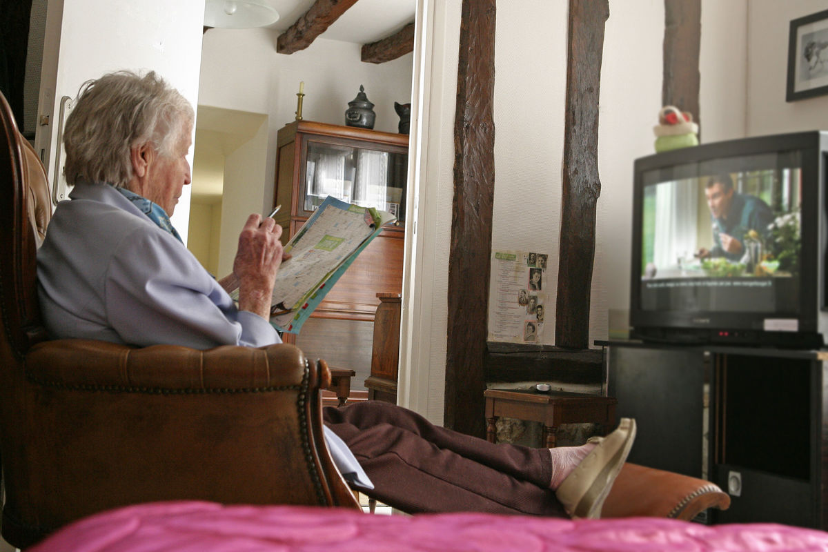 senior woman watching tv by herself at home