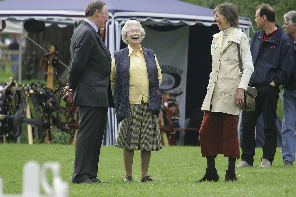 Queen Elizabeth II (C) enjoying the occasion with Michael Bullen, Chairman of the Windsor Horse Show and his wife Sally on the first day of the Royal Windsor Horse Show at Home Park-50833460