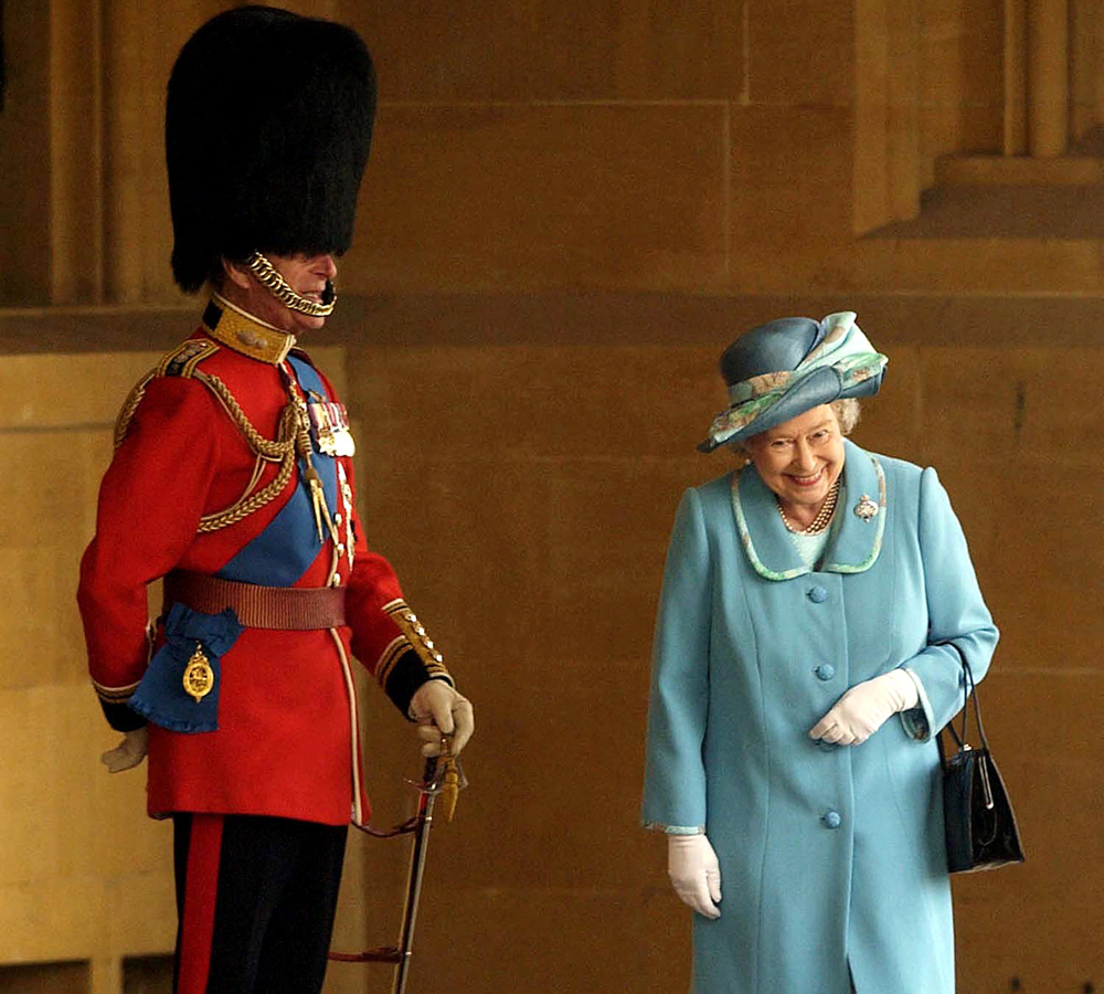 Queen Elizabeth II gets a fit of the giggles as she walks past her husband Prince Philip, the Duke of Edinburgh who is standing to attention in his uniform and bearskin hat at Buckingham Palace-57098573