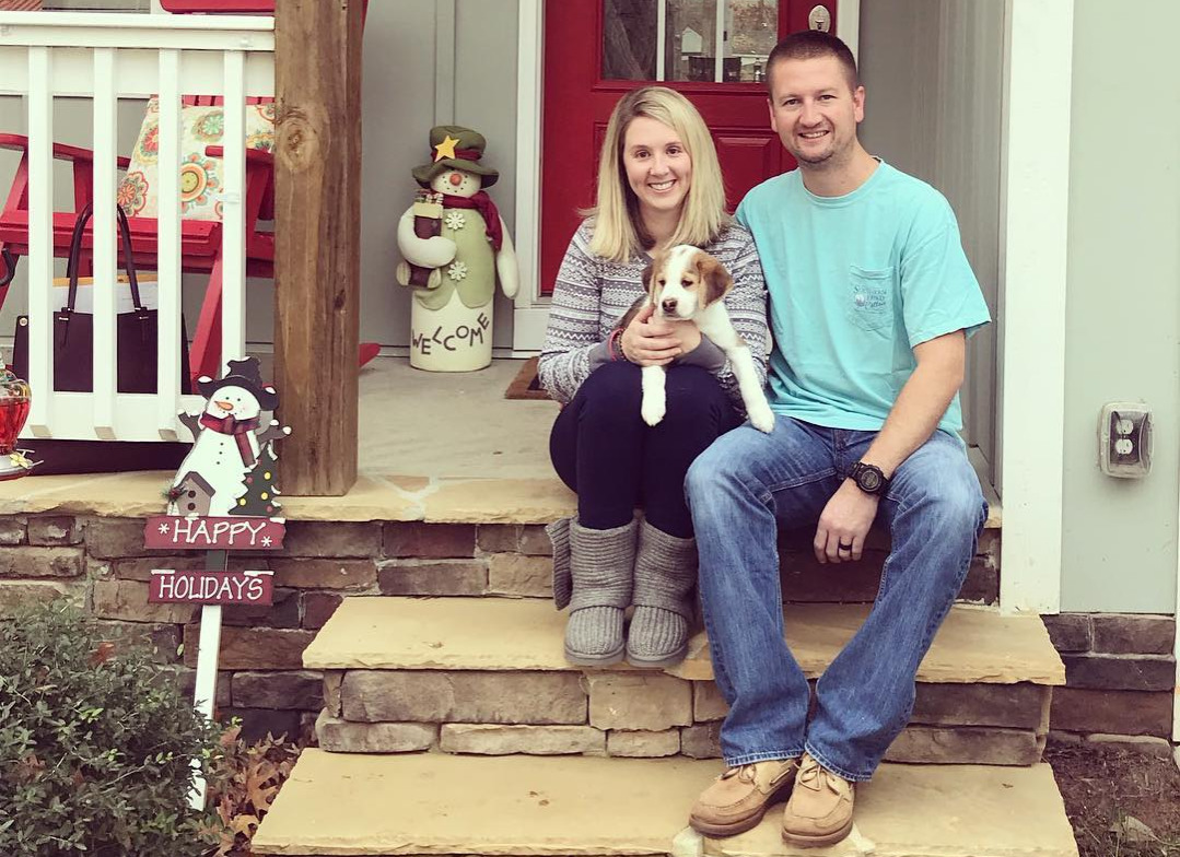 John-and-Katie-Black-with-a-puppy-on-the-steps-of-their-house-51617