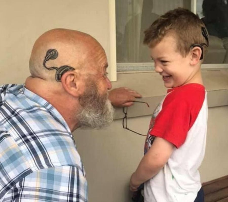 grandfather with cochlea implant tatoo beside grandson with cochlea implant