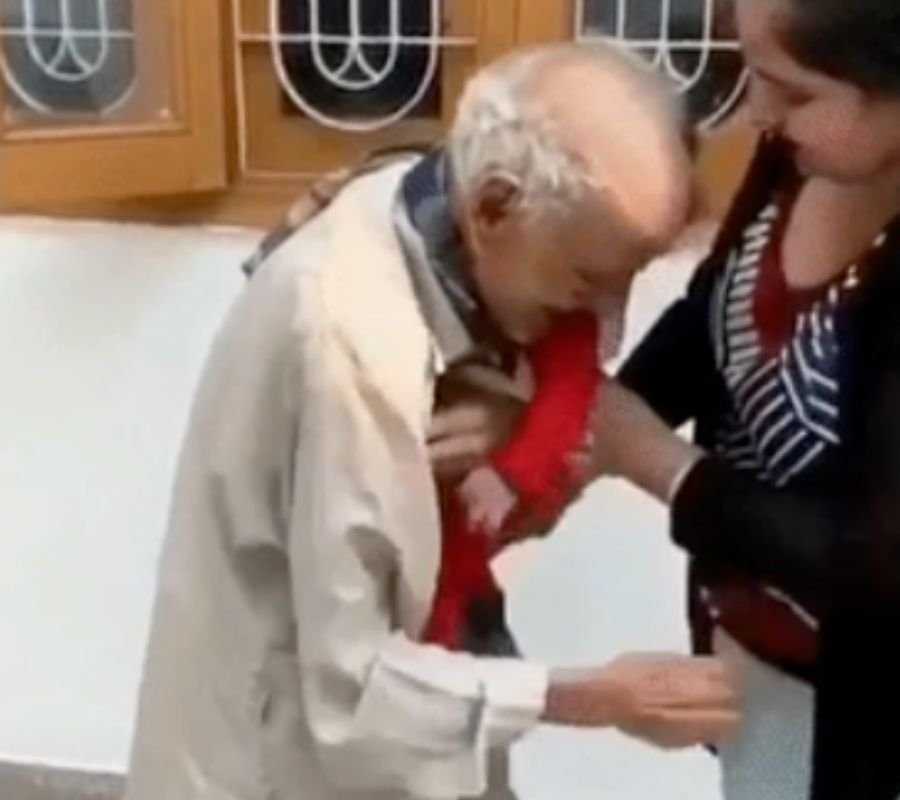 grandfather seeing grandkid picking her up and holding her