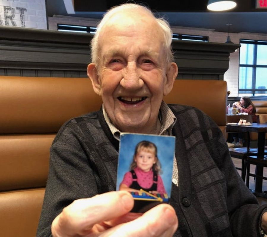 grandpa holding a photo of his granddaughter wallet sized