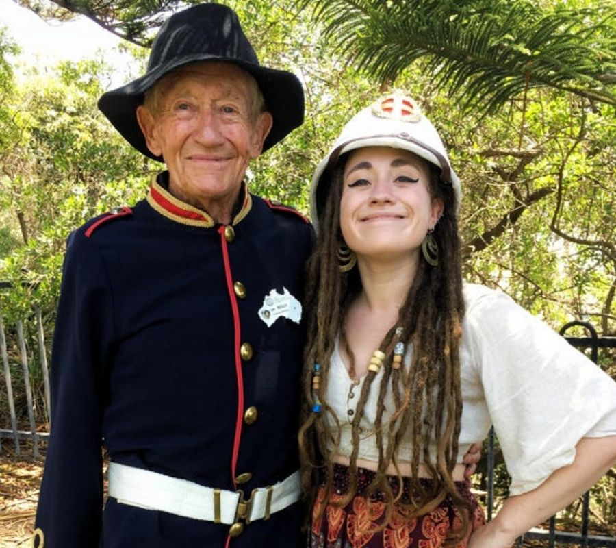 granfather and granddaughter she's wearing a military hat and he's wearing a floppy fashion hat