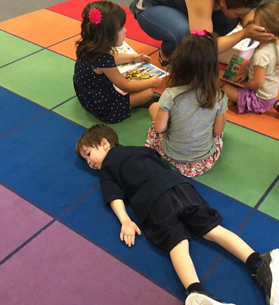 son lies down on a rainbow preschool carpet