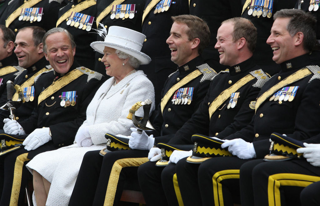 Queen Elizabeth II and Brigadier Mel Jamieson (second left) laugh as an officers group picture is taken