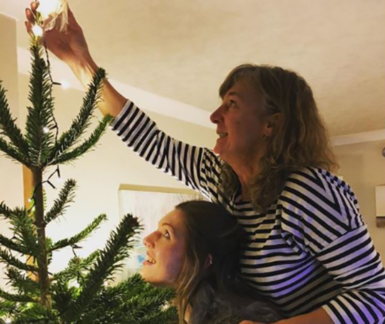 Heidi and Kay Parker placing the star on a Christmas tree