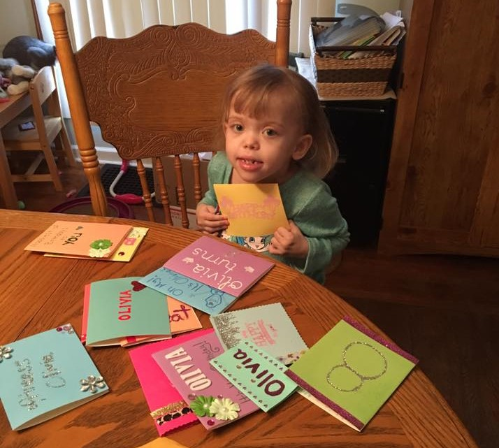 Olivia holds a birthday card to her chest while sitting at a table covered with more cards.