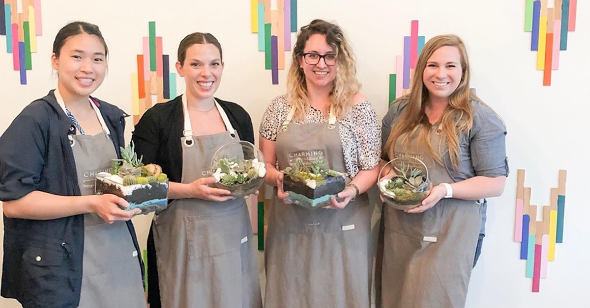 four women wearing aprons and holding succulents