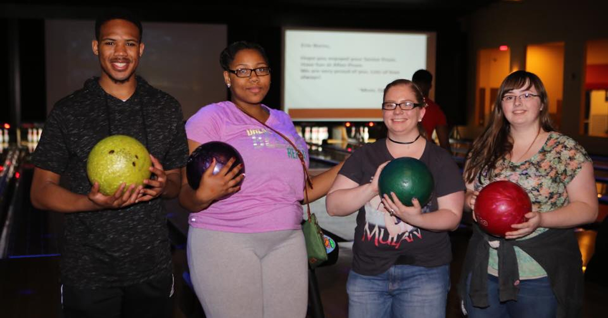 four people holding bowling balls