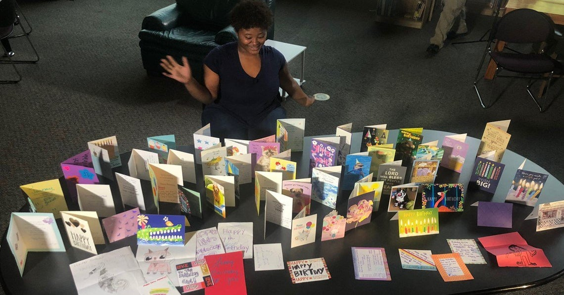 Teenager Jainay sits behind a table full of her birthday cards, looking at them and smiling.