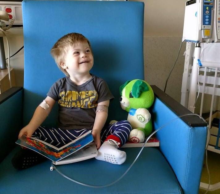 Freddie holds a book open in his lap and looks up smiling while he receives chemotherapy.