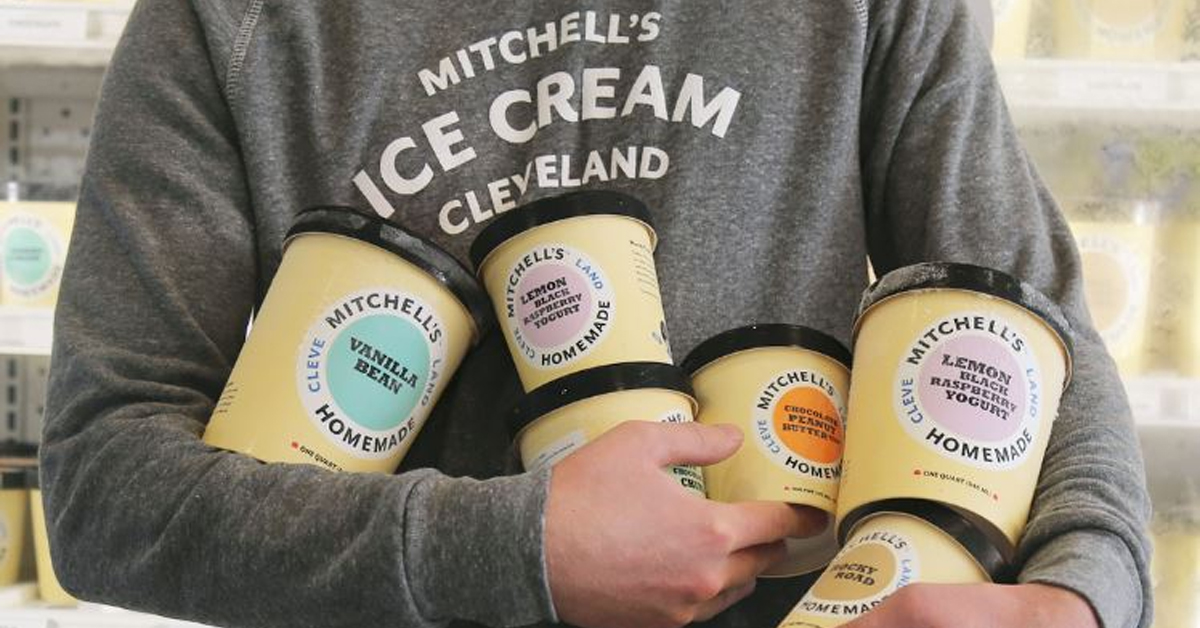 a person holding a bunch of pints of ice cream
