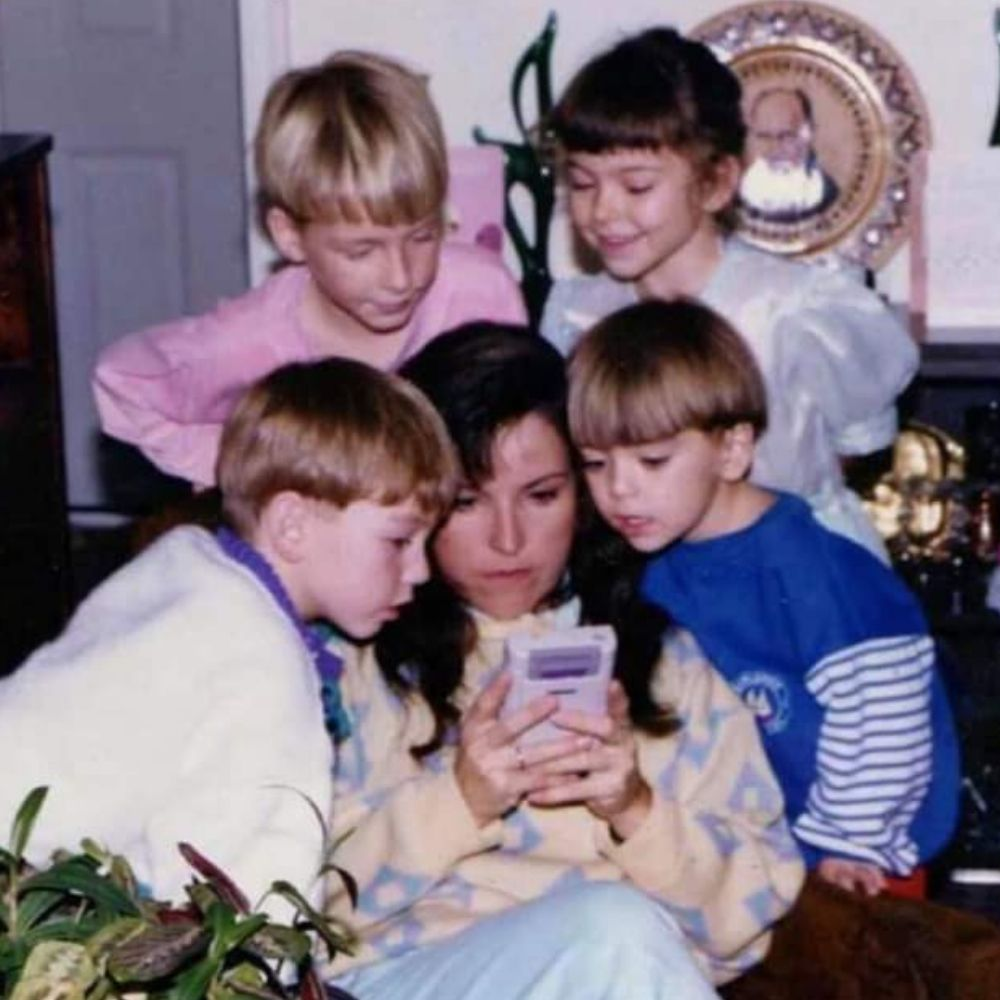 mom playing gameboy for her children