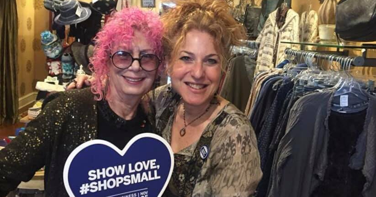 two women in a boutique holding a sign that says show love, #shopsmall