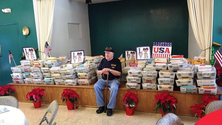 Veteran Dwayne sits on a low stage alongside dozens of containers that are full of cards.