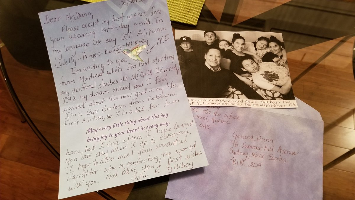 John's card lays open on a table next to a photograph of the his family.