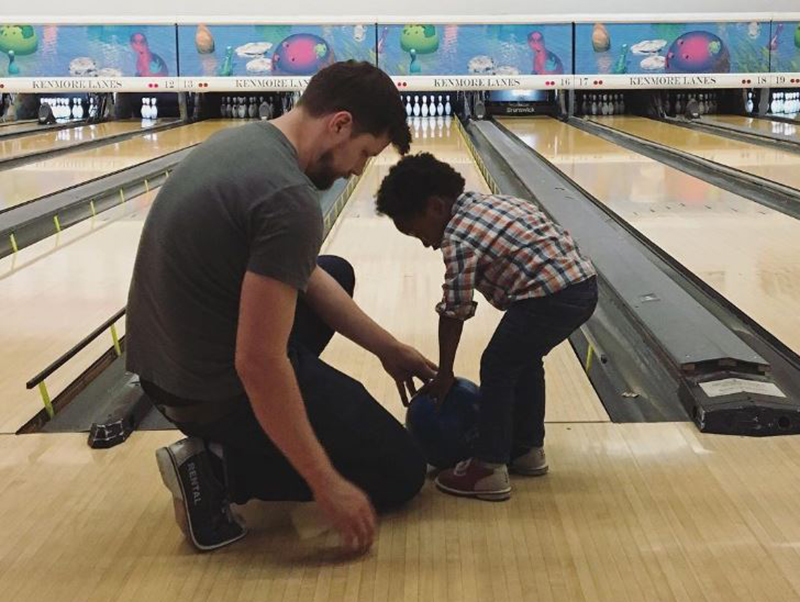 Stuart Shank teachers his young foster son how to bowl