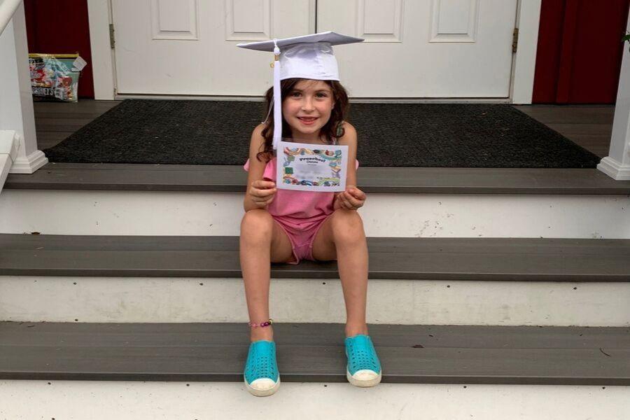 Sophia Garabedian sits on a set of steps with a kindergarten graduation cap on