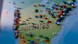 A US map with pushpins scattered in it