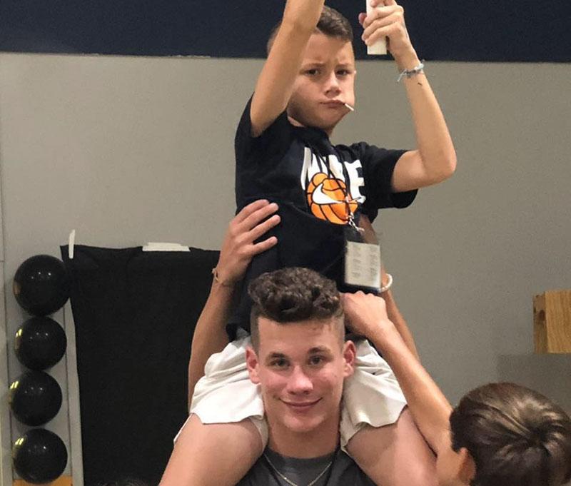 Max sits on Noah's shoulder and pantemimes shooting a basketball