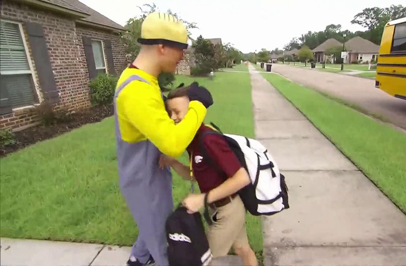 Noah dressed like a minion pulls Max's smiling face in for a hug