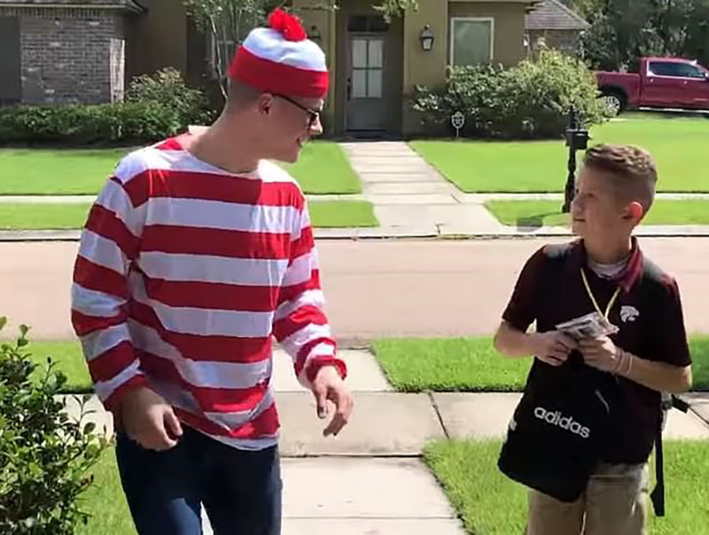 Noah, dressed like Where's Waldo, smiles through fake glasses as Max while they walk towards the front door