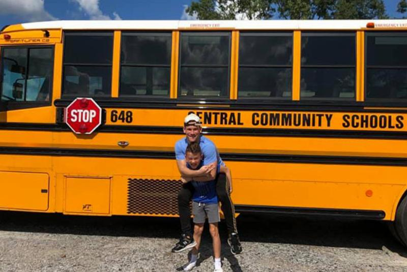 Max wears a tense expression on his face while carrying Noah on his back in front of a school bus
