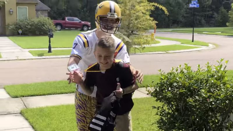 Noah dressed as a football player guides the laughing Max inside